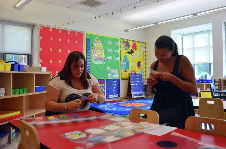 Pre-kindergarten teachers Kristin I'Orio, at left, and Tara Lanese work on finishing name tags for their students at Tokeneke Elementary School. Photo: Megan Spicer / Darien News