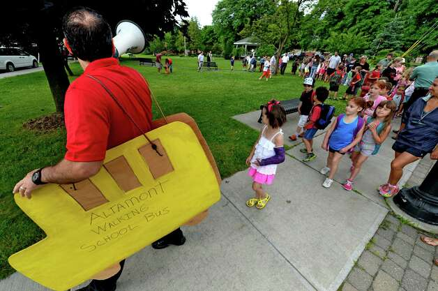 """Altamont Elementary School principal Pete Brabant leads a group walk to school which they call the """"walking school bus"""" Tuesday morning, June 24, 2014, in Altamont, N.Y. (Skip Dickstein / Times Union) Photo: SKIP DICKSTEIN / 00027470A"""