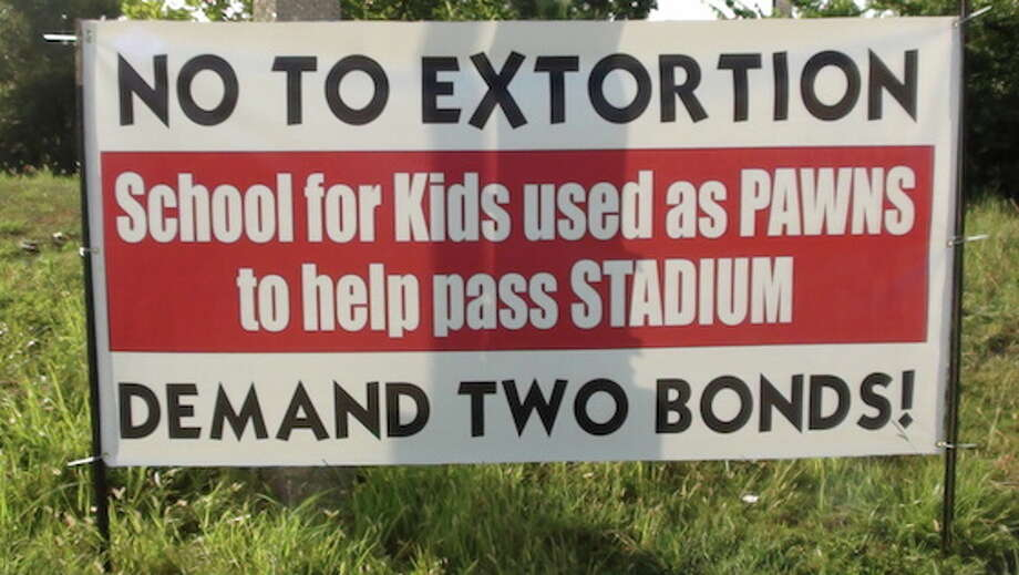 Protest signs were put up outside Second Baptist Church West at I-10 near S Greenhouse Road Tuesday calling for a second bond featuring just the proposed new stadium.. Photo: Michel Franks