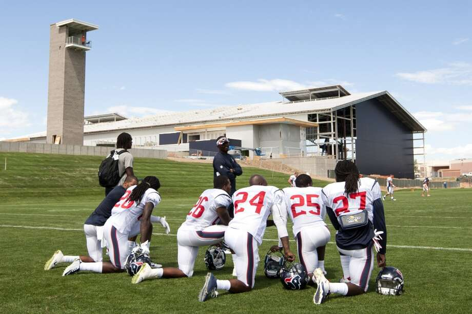 Texans defensive backs take a knee in the end zone following a joint practice. Photo: Brett Coomer, Houston Chronicle