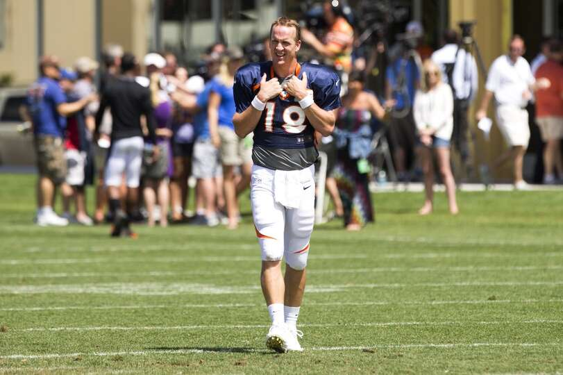 Broncos quarterback Peyton Manning (18) walks across the field following a joint practice.