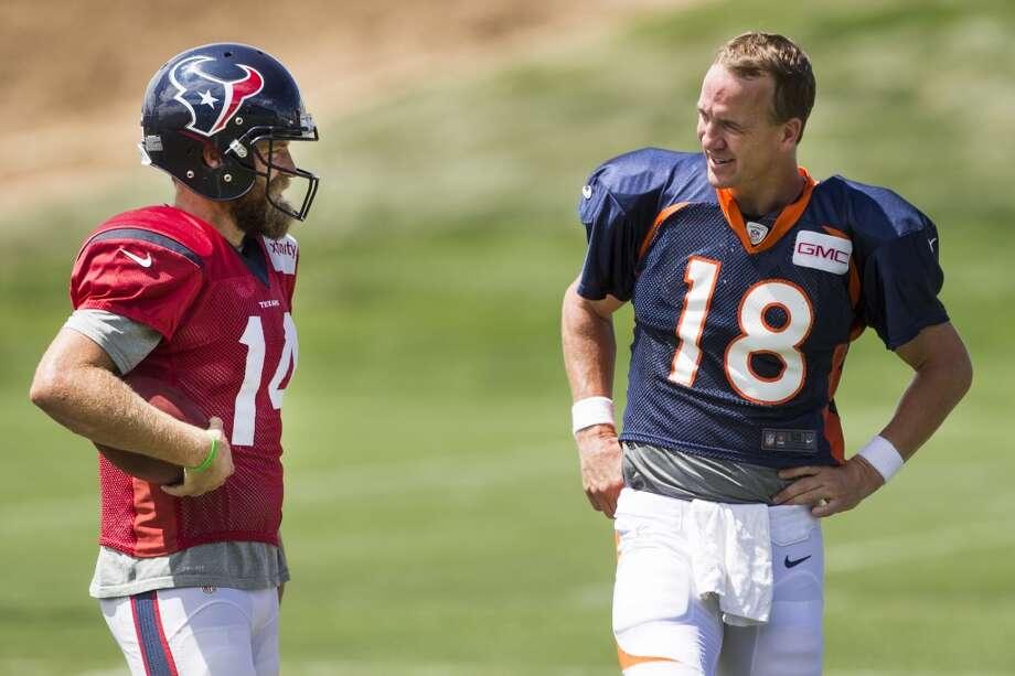 Texans quarterback Ryan Fitzpatrick (14) talks to Broncos quarterback Peyton Manning (18) following a joint practice. Photo: Brett Coomer, Houston Chronicle