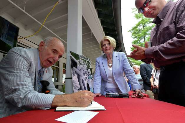 Master of marketing Ed Lewi, left signs his book of memories Wednesday afternoon Aug. 20, 2014,  at the Saratoga Race Course in Saratoga Springs, N.Y.  With Lewi is his wife Maureen , center.  (Skip Dickstein/Times Union) Photo: SKIP DICKSTEIN