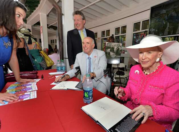 Ed Lewi signs his book of marketing memories  and is joined by his friend Mary Lou Whitney, right, Wednesday afternoon Aug. 20, 2014,  at the Saratoga Race Course in Saratoga Springs, N.Y.    (Skip Dickstein/Times Union) Photo: SKIP DICKSTEIN