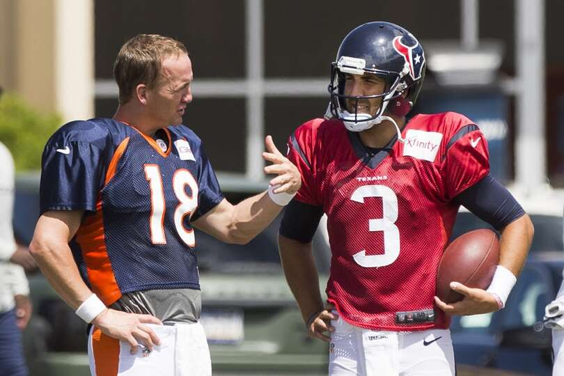 Broncos quarterback Peyton Manning (18) talks to Texans quarterback Tom Savage (3) following a joint