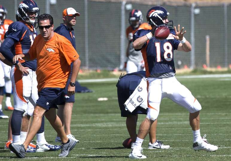 Broncos and former Houston Texans quarterbacks coach Greg Knapp, left, walks past quarterback Peyton