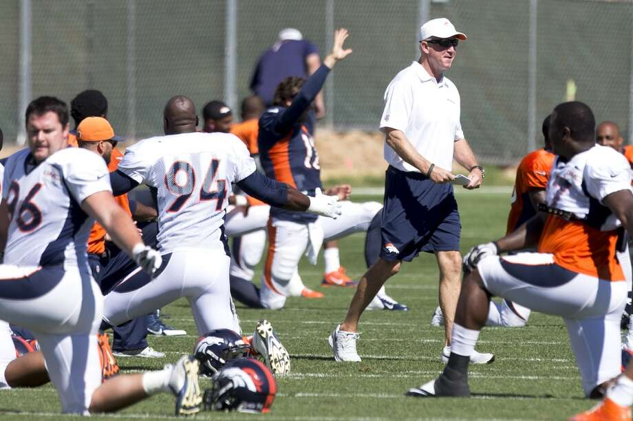 Broncos head coach John Fox walks across the field as his team stretches . Photo: Brett Coomer, Houston Chronicle