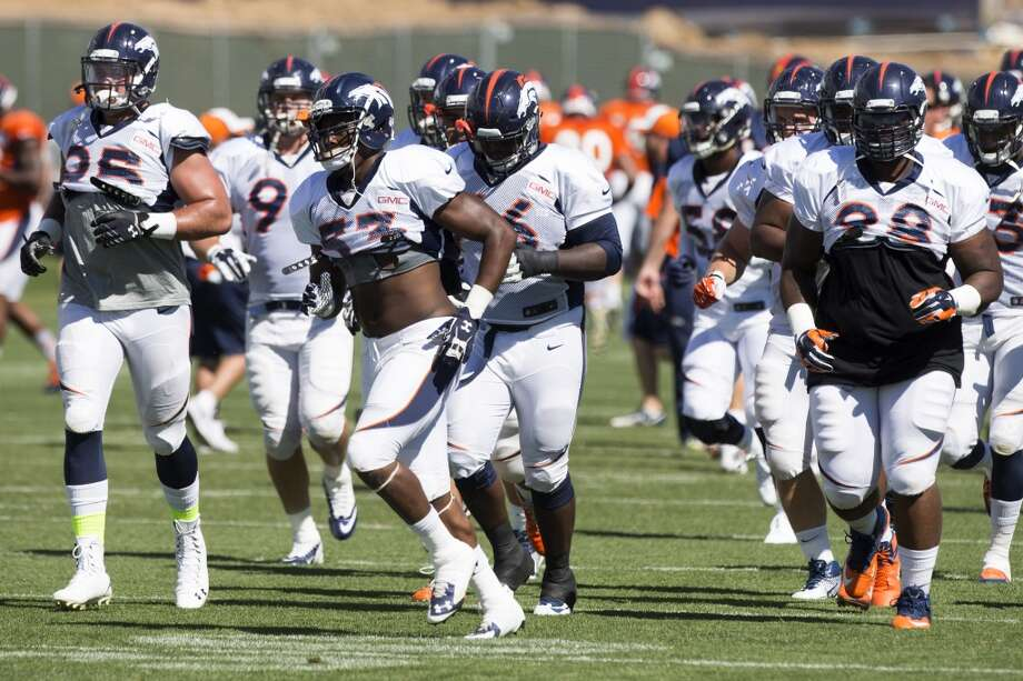 Broncos players run to their next drill. Photo: Brett Coomer, Houston Chronicle