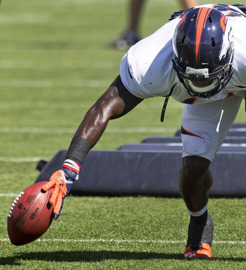 Broncos defensive back Charles Mitchell knocks a ball back inbounds while running a fumble drill.