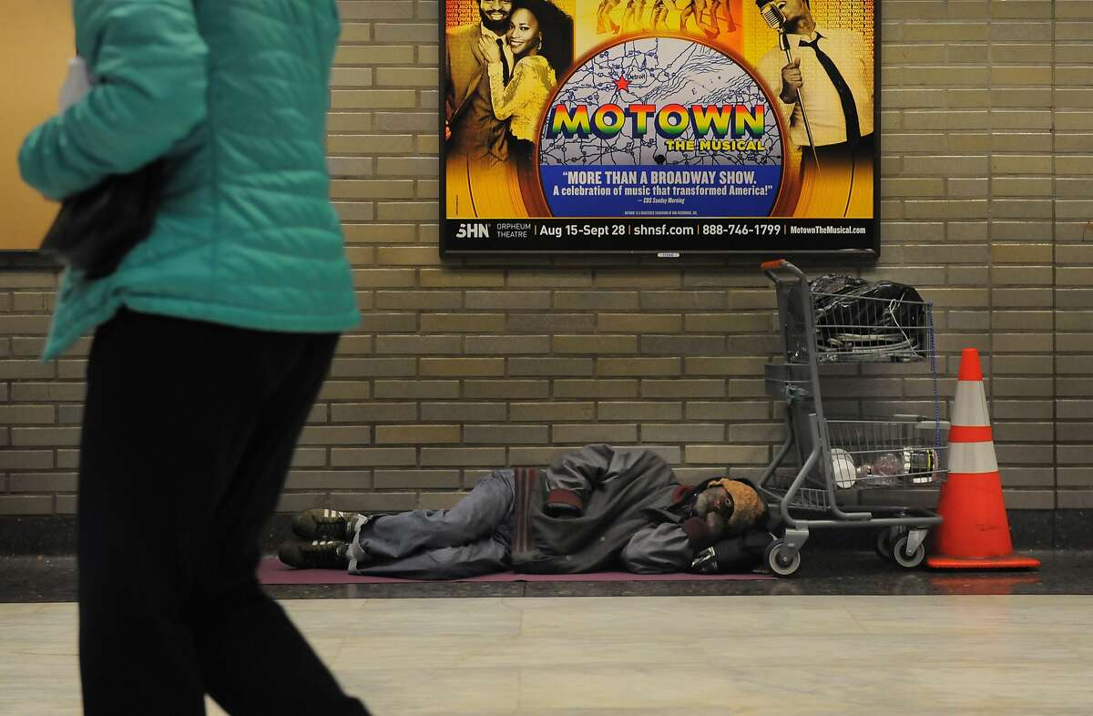 A homeless man sleeps inside the Civic Center BART station on August 20, 2014 in San Francisco, CA.
