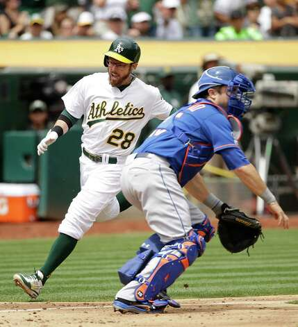 Oakland Athletics' Eric Sogard, left, comes in to score the A's first run as New York Mets catcher Travis d'Arnaud, right, waits for the throw during the third inning of their interleague baseball game Wednesday, Aug. 20, 2014, in Oakland, Calif. Sogard after the Athletics' Coco Crisp doubled. (AP Photo/Eric Risberg) ORG XMIT: OAS109 Photo: Eric Risberg / AP