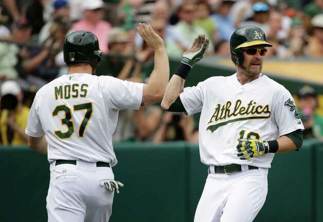 Oakland Athletics' Josh Reddick, right, is greeted by teammate Brandon Moss, left, after scoring in the fourth inning of their interleague baseball game against the New York Mets Wednesday, Aug. 20, 2014, in Oakland, Calif. Both Reddick and Moss scored after the Athletics' Andy Parrino reached on a fielding error by Mets second baseman Daniel Murphy. (AP Photo/Eric Risberg) ORG XMIT: OAS111 Photo: Eric Risberg / AP