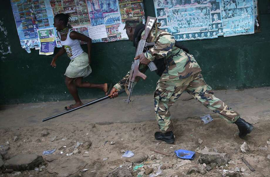 A Liberian army soldier, part of the Ebola Task Force, beats a local resident while enforcing a quarantine on the West Point slum in Monrovia. Photo: Getty Images / 2014 Getty Images