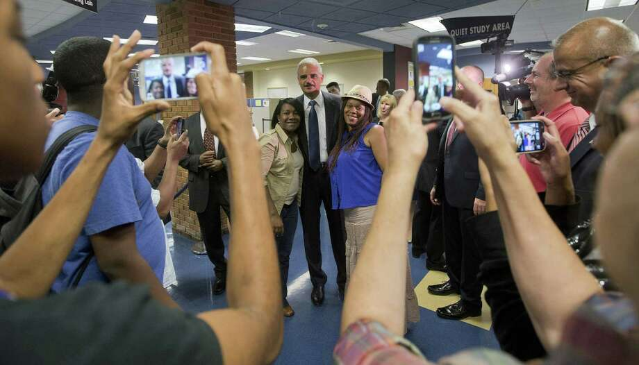 U.S. Attorney General Eric Holder, center, poses for photographs following his meeting with students at St. Louis Community College Florissant Valley. Photo: Pool / 2014 Getty Images