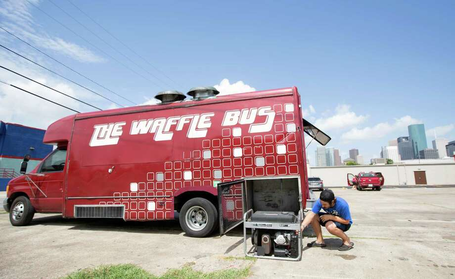 Austin Clark checks on the generator of The Waffle Bus in the 1500 block of St. Emanuel on Wednesday. Food truck operators support changes to allow the trucks in public spaces downtown. Photo: Cody Duty, Staff / © 2014 Houston Chronicle