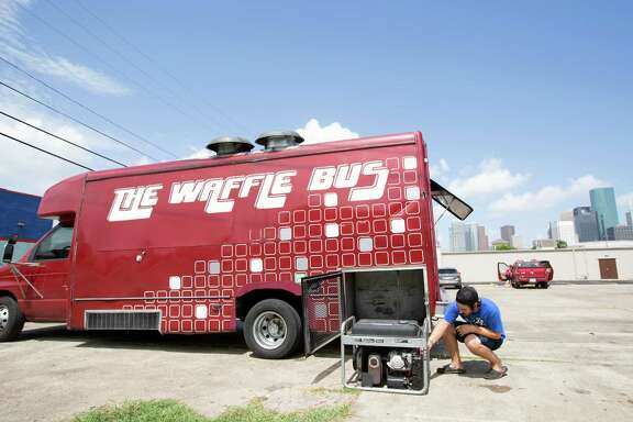Austin Clark checks on the generator of The Waffle Bus in the 1500 block of St. Emanuel on Wednesday. Food truck operators support changes to allow the trucks in public spaces downtown.