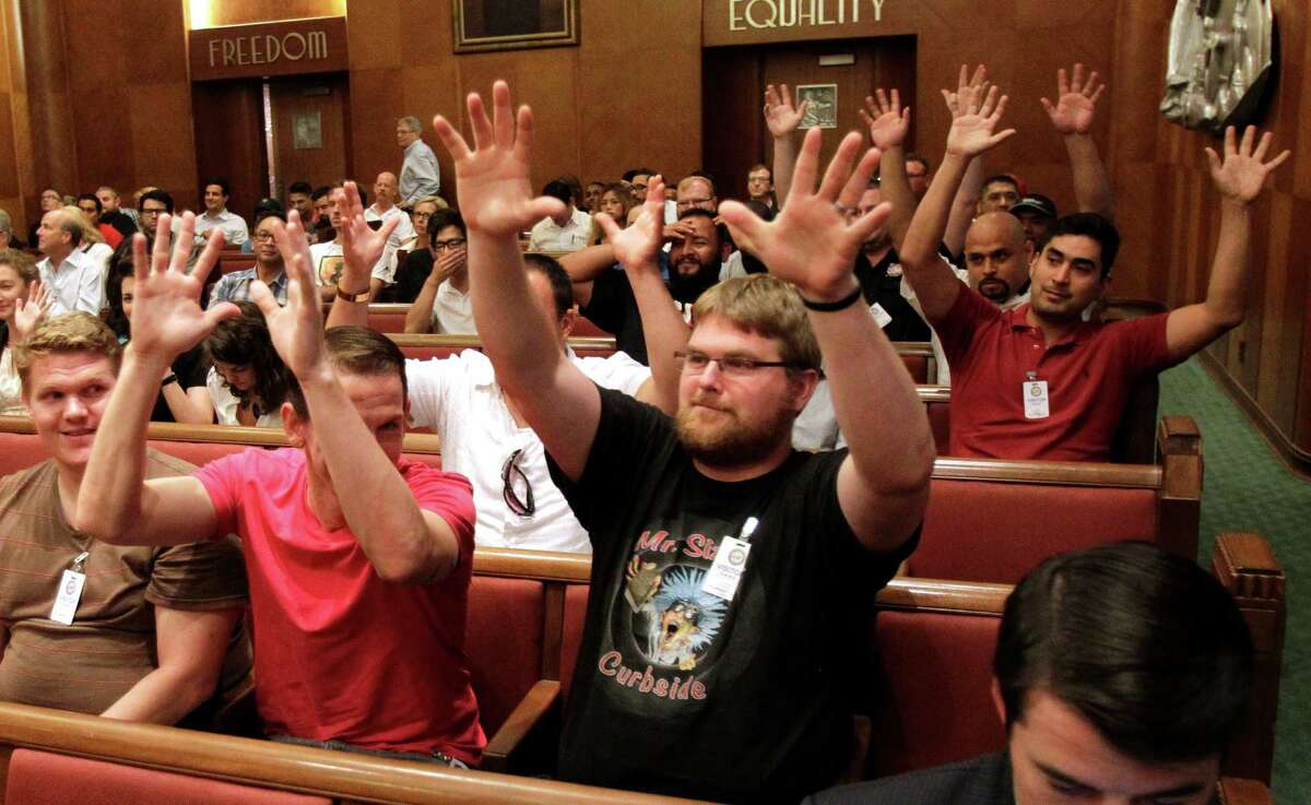 Andrew Shiel, center, and other supporters signal their agreement with comments at Wednesday's public hearing.