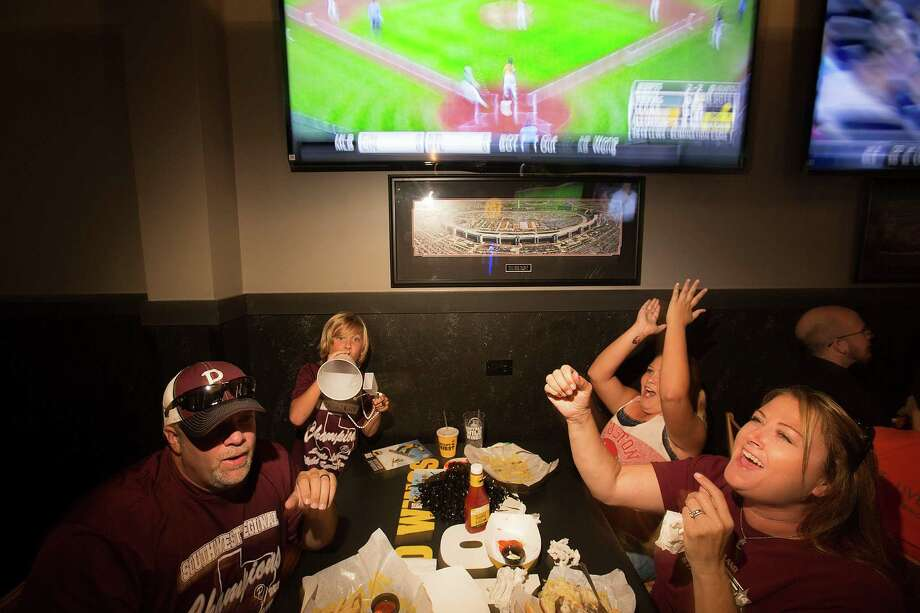 Stephen Borden, his wife, Vige, and children, Cash, 8, and Bayleigh, 11, react to a play while watching Pearland East play Chicago's Jackie Robinson West in the Little League World Series on Tuesday. Photo: Johnny Hanson, Staff / © 2014  Houston Chronicle
