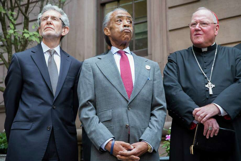 Rev. Al Sharpton, center, attends a press conference alongside Rabbi Michael Miller, left, Executive VP and CEO of the Jewish Community Relations Council of NY,  and Cardinal Timothy Dolan, right,  following a multi-faith roundtable meeting Wednesday, Aug. 20, 2014, in New York, spawned by the death of Eric Garner, a Staten Island man who was placed in an apparent chokehold by a police officer, The mayor says he believes the meeting can help a city gripped by protests and distrust of the police in some minority neighborhoods. (AP Photo/John Minchillo) ORG XMIT: NYJM204 Photo: John Minchillo / FR170537 AP