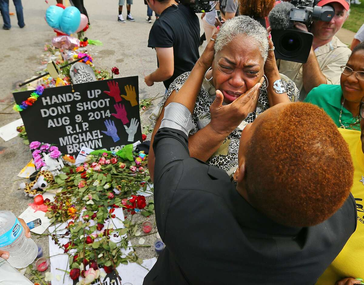 Spiritual teacher Iyanla Vanzant, right, consoles Shirley Scale, a resident at the Canfield Apartments, at the shrine to Michael Brown where he was shot and killed on Wednesday, Aug. 20, 2014, in Ferguson, Mo. Vanzant, from the