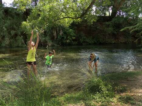 Natalie Carlson (left), Nicholas Carson and Heather Tompkins play in the old channel of the Comal River in Landa Park, New Braunfels on Friday, Aug. 15, 2014. Non-native plant species have been removed from this portion of the channel. Photo: Billy Calzada, San Antonio Express-News / San Antonio Express-News