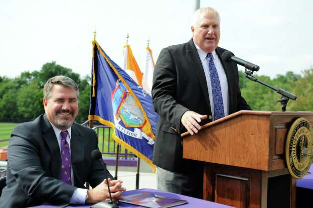 UAlbany's head football coach Greg Gattuso, right, welcomes Mark Benson, left, who was named as UAlbany's new director of athletics Tuesday morning, Aug. 20, 2014, during a news conference at Bob Ford Field in Albany, N.Y. (Cindy Schultz / Times Union) Photo: Cindy Schultz / 00028260A