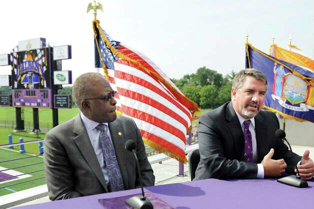 UAlbany president Robert J. Jones, left, joins Mark Benson, right, who was named as UAlbany's new director of athletics during a news conference on Tuesday, Aug. 20, 2014, at Bob Ford Field in Albany, N.Y. (Cindy Schultz / Times Union) Photo: Cindy Schultz / 00028260A