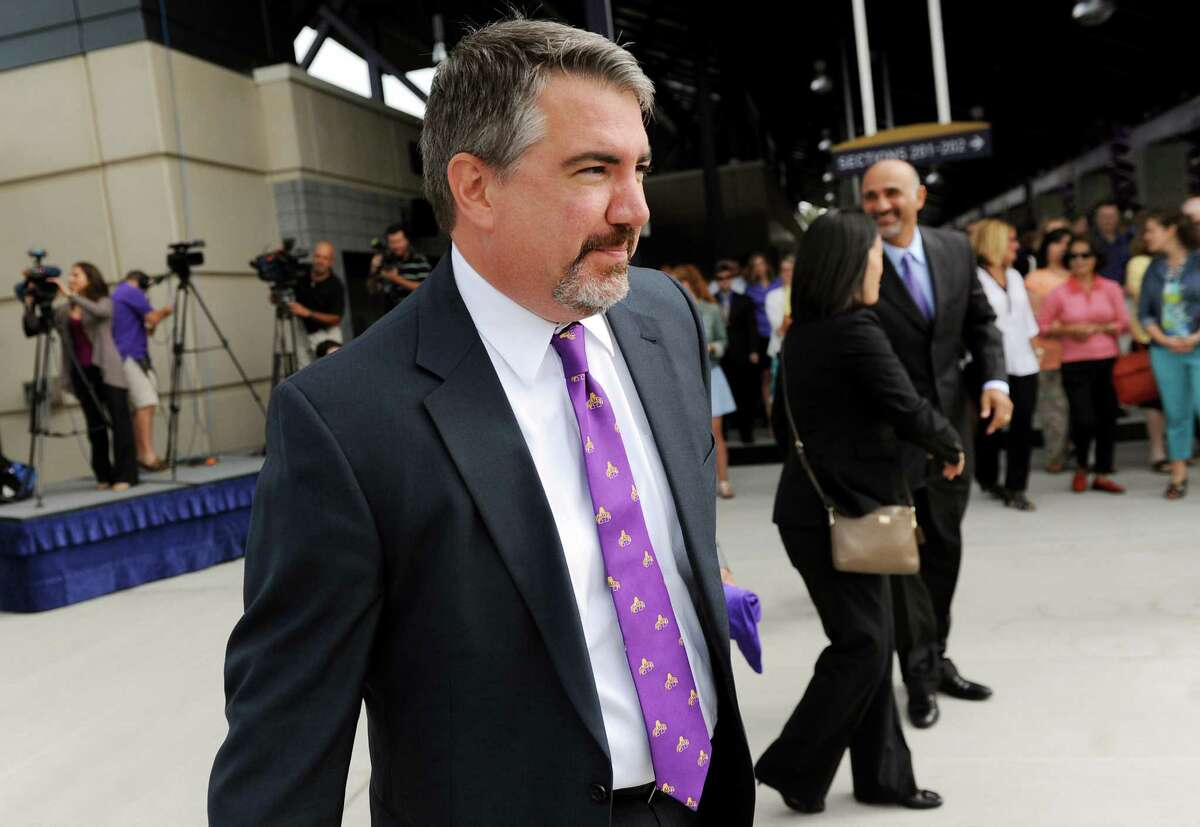 Mark Benson, center, arrives for a news conference where he's named UAlbany's new director of athletics on Tuesday, Aug. 20, 2014, at Bob Ford Field in Albany, N.Y. (Cindy Schultz / Times Union)