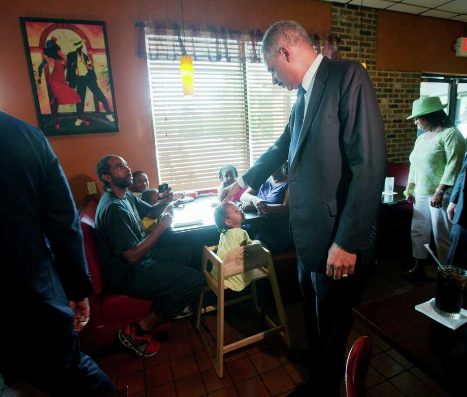 Attorney General Eric Holder touches the forehead of Yusayrah Jones, 2, has he arrives at Drake's Place Restaurant for a meeting with community leaders, Wednesday, Aug. 20, 2014 in Florrissant, Mo. Holder arrived in Missouri on Wednesday, a small group of protesters gathered outside the building where a grand jury could begin hearing evidence to determine whether a Ferguson police officer who shot 18-year-old Michael Brown should be charged in his death.   (AP Photo/Pablo Martinez Monsivais, Pool)  ORG XMIT: MOPM111 Photo: Pablo Martinez Monsivais / AP Pool
