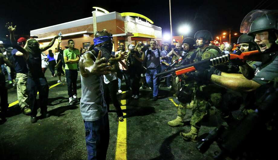 Early Wednesday, police officers move in to clear crowds in Ferguson, Mo., a suburb of St. Louis where on Aug. 9 a white policeman fatally shot Michael Brown, an unarmed black 18-year-old. Photo: Curtis Compton / Associated Press / Atlanta Journal-Constitution