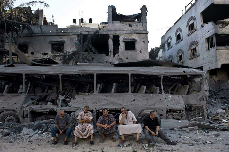 Five Palestinian men on Wednesday sit next to a destroyed bus that was targeted by Israeli airstrikes the day before. The houses nearby also were bombed in the attack. Photo: Roberto Schmidt / Getty Images / AFP