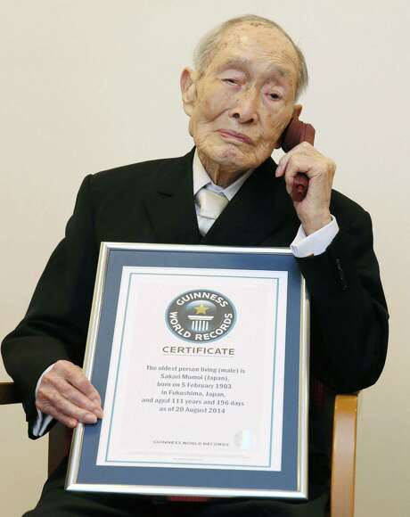 Sakari Momoi, a 111-year-old Japanese retired educator, poses for a photo after receiving a certificate from Guinness World Records, in Tokyo Wednesday, Aug. 20, 2014. Momoi was recognized as the world's oldest living man on Wednesday, succeeding Alexander Imich of New York, who died in April at the age of 111 years, 164 days. (AP Photo/Kyodo News) JAPAN OUT, CREDIT MANDATORY Photo: SUB / Kyodo News