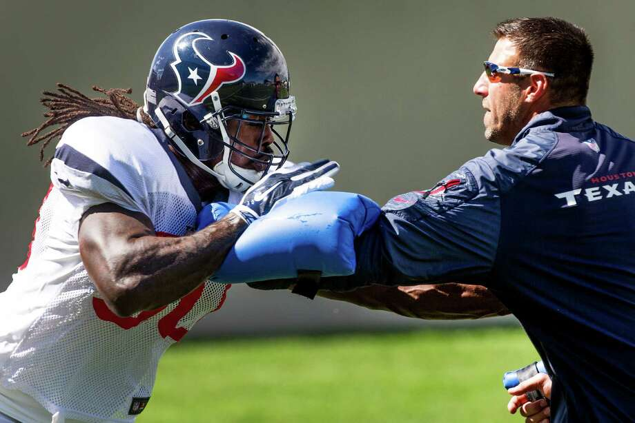 Jadeveon Clowney runs a drill with linebackers coach Mike Vrabel before sitting out the end of practice with an injury that didn't appear to be serious. Photo: Brett Coomer, Staff / © 2014 Houston Chronicle