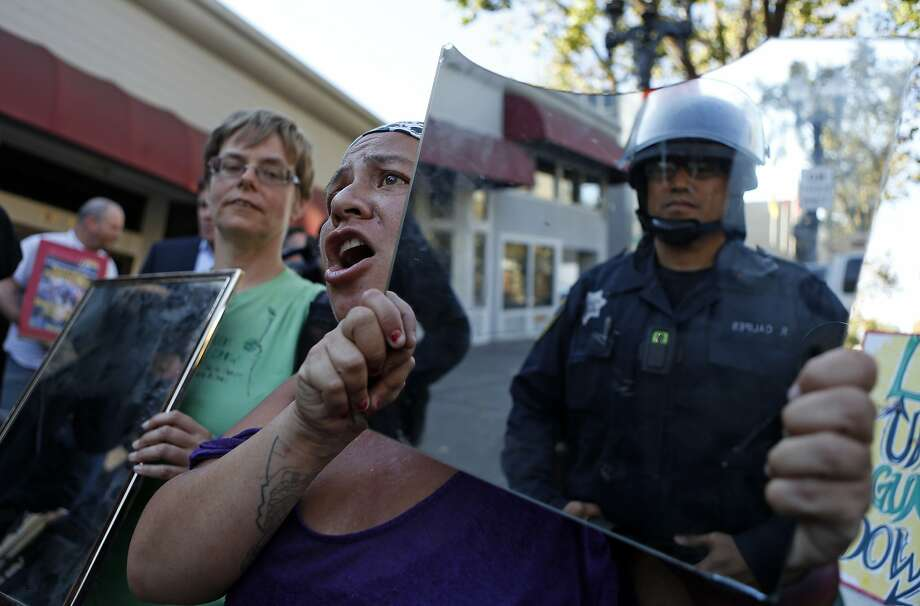 Demonstrators supporting protesters in Ferguson, Mo., hold up mirrors to police during a march Wednesday in Oakland. Photo: Scott Strazzante, The Chronicle