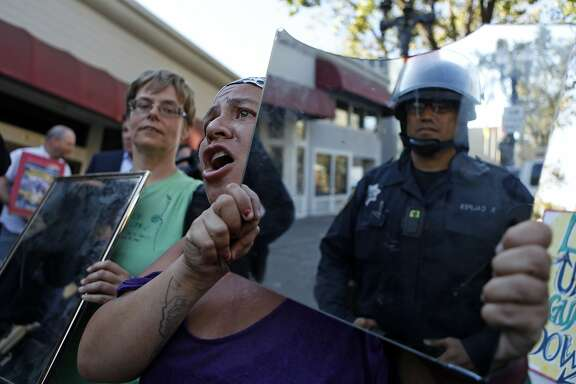 Protesters in support of Ferguson, Missouri residents hold up mirrors to the police after being stopped from marching to police headquarters in Oakland, Calif. on Wednesday, August 20, 2014.