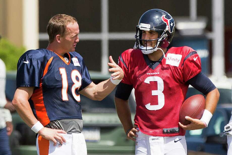 While tempers flared in several corners of the field when the Texans and Broncos worked out together Wednesday, quarterback Peyton Manning, left, remained above the fray, even taking time to talk to rookie Tom Savage. Photo: Brett Coomer, Staff / © 2014 Houston Chronicle