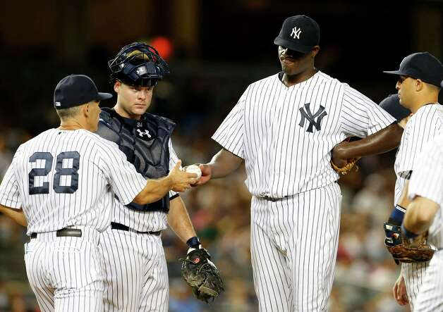 NEW YORK, NY - AUGUST 20:  Michael Pineda #35 of the New York Yankees hands the ball to manager Joe Girardi #28 as he is taken out of the game in the seventh inning against the Houston Astros as catcher Brian McCann #34 looks on during a MLB baseball game at Yankee Stadium on August 20, 2014 in the Bronx borough of New York City. (Photo by Rich Schultz/Getty Images) ORG XMIT: 477588359 Photo: Rich Schultz / 2014 Getty Images