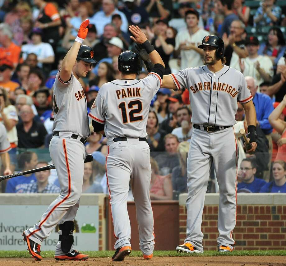 CHICAGO, IL - AUGUST 20: Joe Panik #12 of the San Francisco Giants is greeted by Andrew Susac (L) and Michael Morse #38  after scoring against the Chicago Cubs during the first inning on August 20, 2014 at Wrigley Field in Chicago, Illinois.  (Photo by David Banks/Getty Images) Photo: David Banks, Getty Images