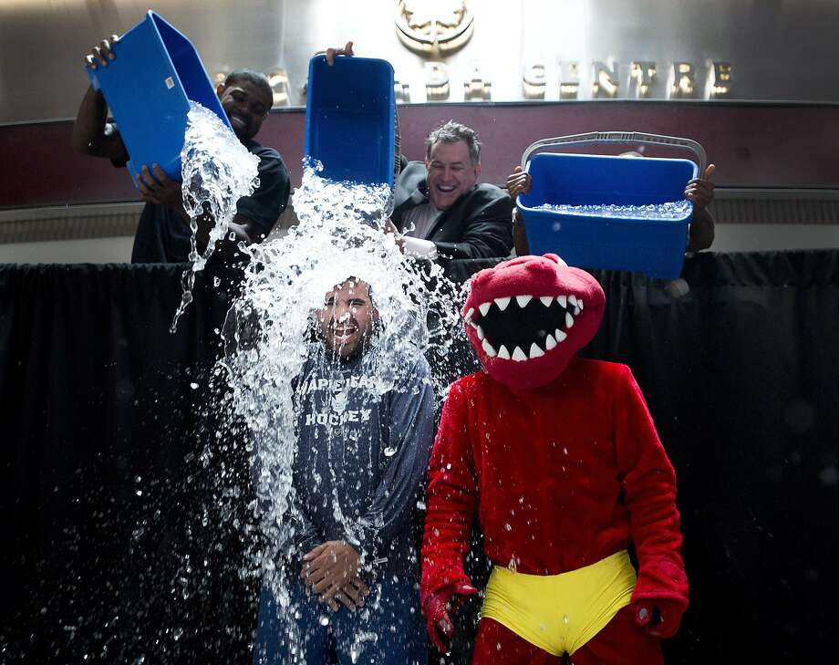 Nazem Kadri, bottom left, of the Maple Leafs and the Raptor, bottom right, participate in the ALS Ice Bucket Challenge as Jermain Defoe, top right, of Toronto FC, Amir Johnson, left, of the Toronto Raptors and Tim Leiweke, center, President and CEO of Maple Leaf Sports Entertainment dump water on them in Toronto on Wednesday, Aug. 20, 2014. (AP Photo/The Canadian Press, Nathan Denette) Photo: Nathan Denette, Associated Press