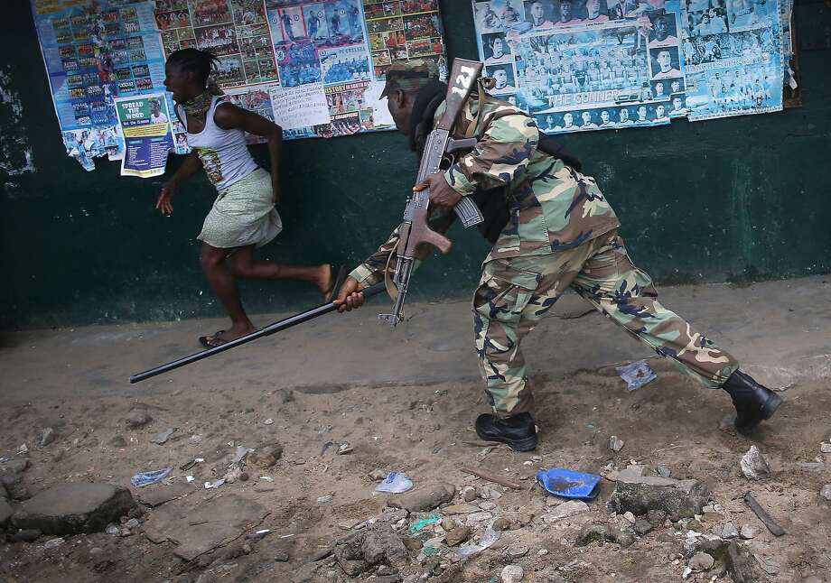 MONROVIA, LIBERIA - AUGUST 20:  A Liberian Army soldier, part of the Ebola Task Force, beats a local resident while enforcing a quarantine on the West Point slum on August 20, 2014 in Monrovia, Liberia. The government ordered the quarantine of West Point, a congested seaside slum of 75,000, on Wednesday, in an effort to stop the spread of the virus in the capital city. Liberian soldiers were also sent in to the seaside favela to extract West Point Commissioner Miata Flowers and her family members after residents blamed the government for setting up a holding center for suspected Ebola patients to be set up in their community. A mob overran and closed the facility on August 16. The military also began enforcing a quarrantine on West Point, a congested slum of 75,000, fearing a spread of the epidemic. The Ebola virus has killed more than 1,200 people in four African nations, more in Liberia than any other country.  (Photo by John Moore/Getty Images) *** BESTPIX *** Photo: John Moore, Getty Images