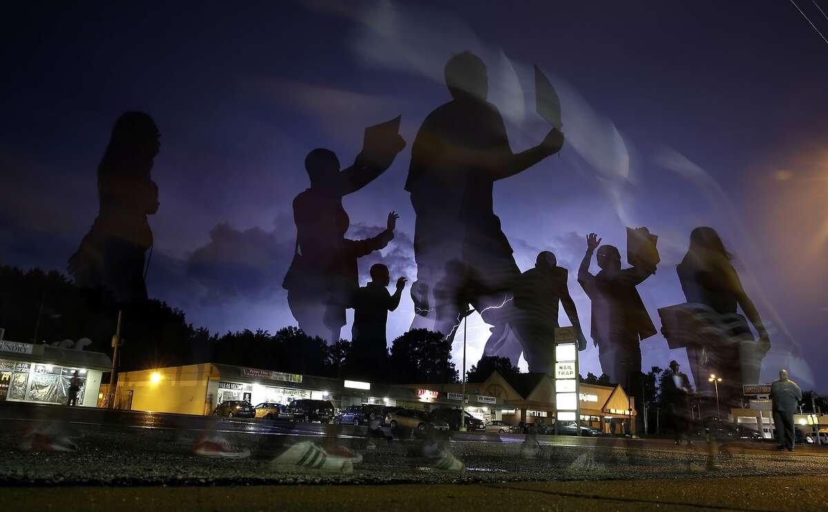 Protesters march in the street as lightning flashes in the distance Wednesday, Aug. 20, 2014, in Ferguson, Mo. A grand jury has begun hearing evidence as it weighs possible charges against the Ferguson police officer who fatally shot 18-year-old Michael Brown. (AP Photo/Jeff Roberson)