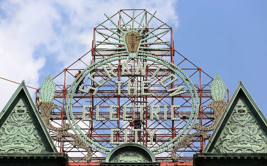 Mac Sign Systems electricians remove old incandescent bulbs and install new LED (light emitting diode) bulbs on the Electric City sign on the Scranton Electric Building in Scranton, Pa., on Wednesday, Aug 20, 2014.  The 1,300 white incandescent bulbs are being replaced with the color scheme from the 1930s but with 21st century LED builds. The 1-watt LED bulbs will drop the annual electric bill some 90 percent.  La Festa Italiana is contributing up to $10,000 to renovate the sign overlooking Courthouse Square, where the three-day celebration of Italian culture and cuisine takes place every Labor Day weekend. (AP Photo/The Times-Tribune, Jake Danna Stevens) Photo: Jake Danna Stevens, Associated Press