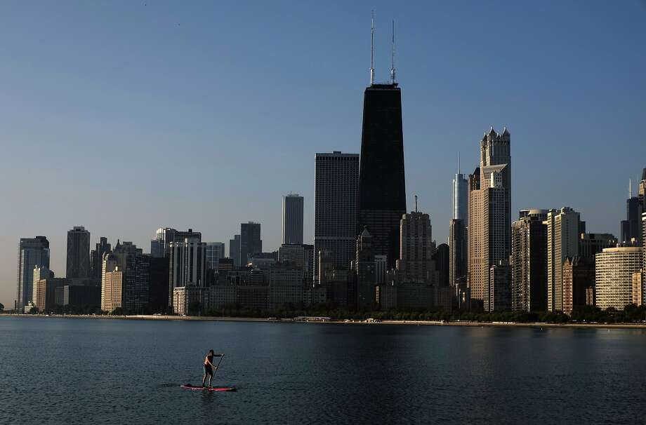 A paddle boarder coasts along the smooth surface of Lake Michigan with the downtown skyline in the background Wednesday morning, Aug. 20, 2014, in Chicago. (AP Photo/Kiichiro Sato) Photo: Kiichiro Sato, Associated Press