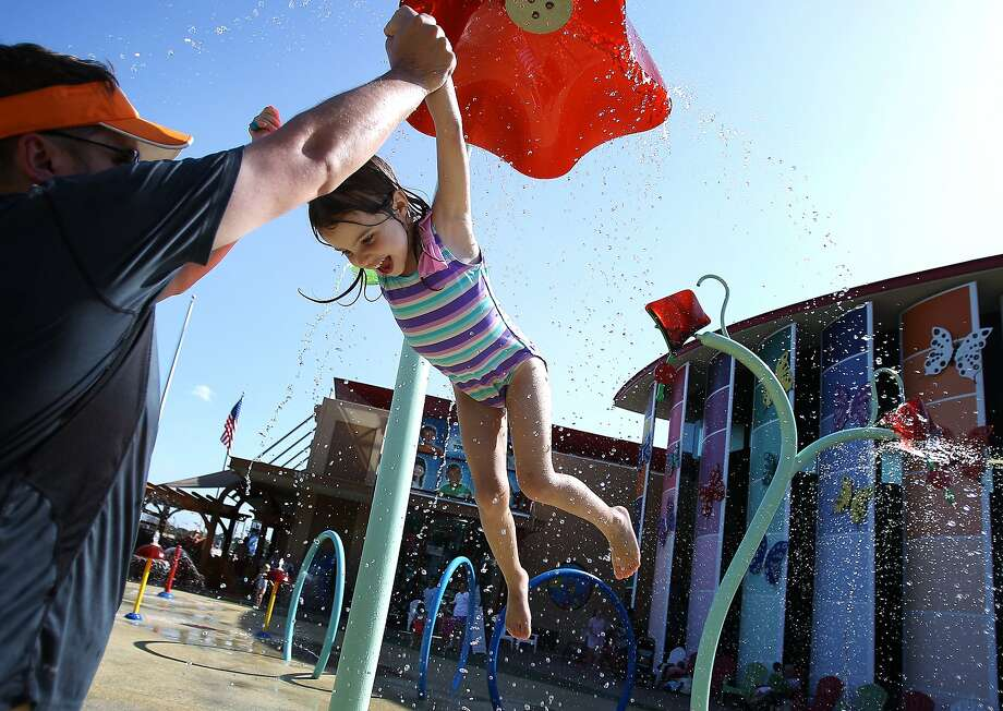 Douse your daughter day at the museum: Four-year-old Abalynn Lyons squeals as dad Rob swings her 