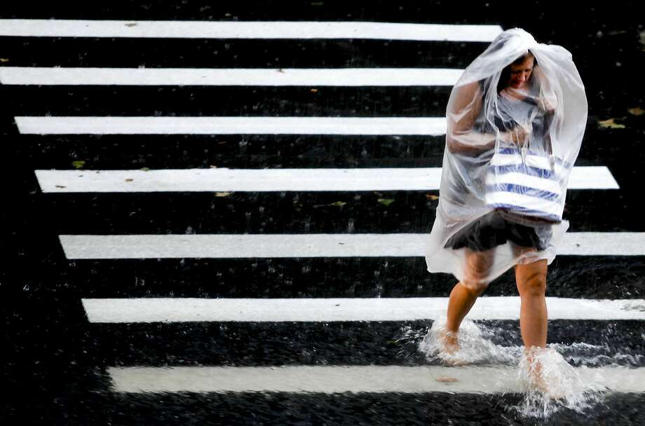 A woman hurries through the rain on Western Kentucky University's campus in Bowling Green, Ky., on Wednesday, Aug. 20, 2014. (AP Photo/The Daily News, Austin Anthony) Photo: Austin Anthony, Associated Press