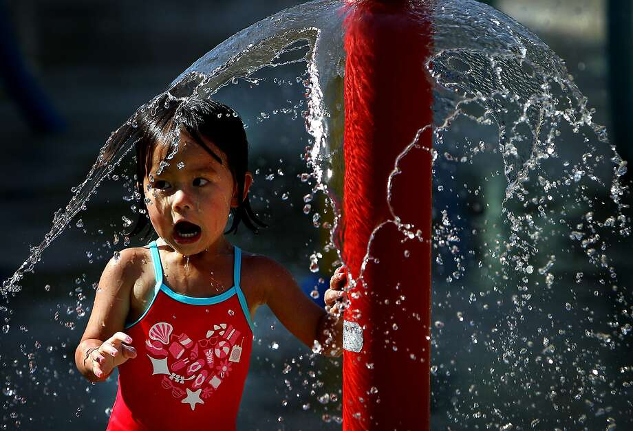 Samantha Do, 2, giggles with delight as she busts through a thin layer of water at the splash park at the Children's Museum of Memphis  in Memphis, Tenn. Wednesday, Aug. 20, 2014. Typical summer weather has returned to Memphis with temperatures expected to hit the upper-90's the rest of the week. (AP Photo/The Commercial Appeal, Mike Brown) Photo: Mike Brown, Associated Press