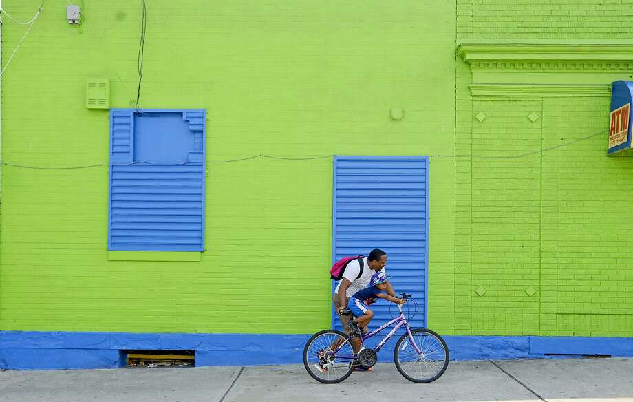Johan Jourdain take his 4-year-old son, Johangel, for a bicycle ride on Oak Street, Wednesday, Aug. 20, 2014, in Paterson, N.J. (AP Photo/The Record of Bergen County, Viorel Florescu) ONLINE OUT; MAGS OUT; TV OUT; INTERNET OUT;  NO ARCHIVING; MANDATORY CREDIT Photo: Viorel Florescu, Associated Press