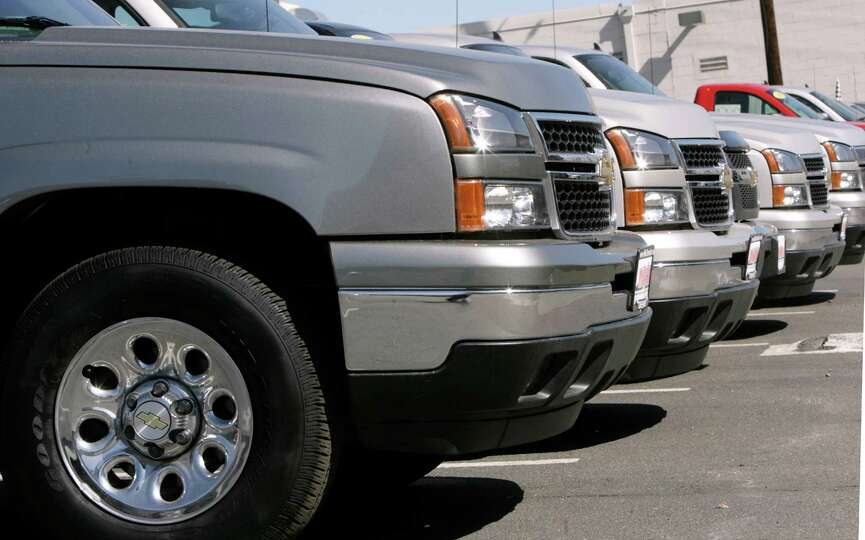 Unsold 2006 pickup trucks sit in a line on the lot of a Chevrolet dealership in Denver on Sunday, Ap