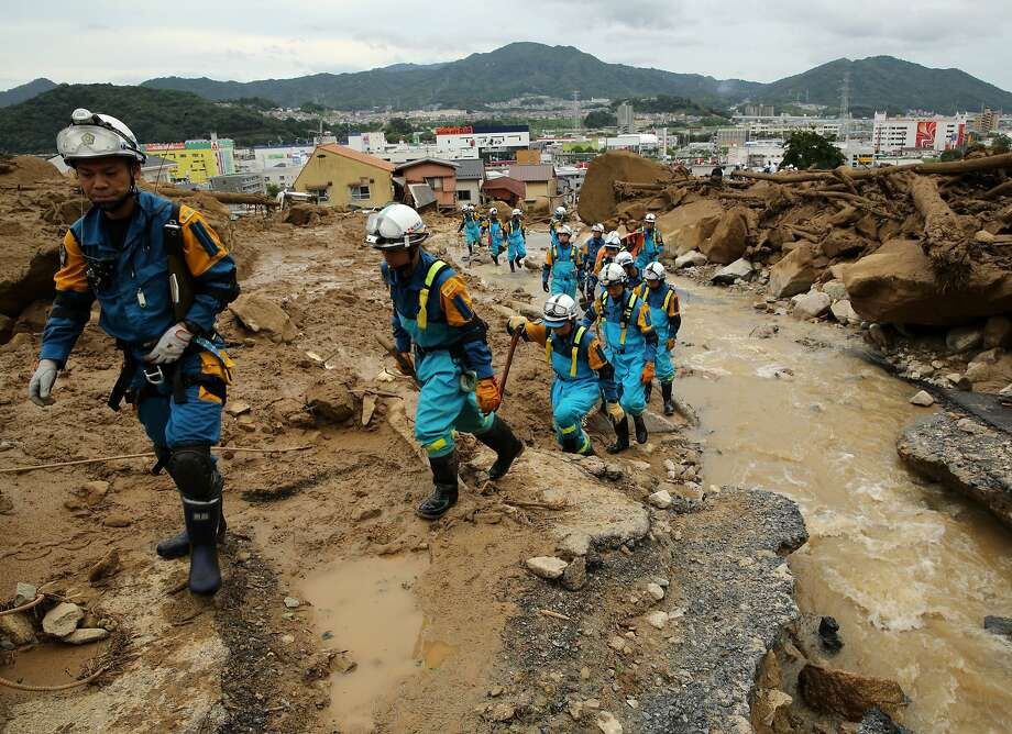 Police drafted as rescuers search for survivors in a residential area ravaged by a mudslide in Hiroshima, Japan. At least 39 people were killed and about 50 missing after torrential rain caused flooding and several landslides in the city. Photo: Buddhika Weerasinghe, Getty Images
