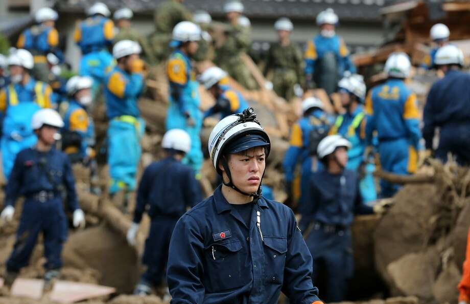 Members of Ground Self-Defense Force, firefighters and police officers continue the search for missing people among the debris of houses destroyed by a landslide caused by torrential rain on August 21, 2014 in Hiroshima, Japan. Rescue work continues as at least 39 people were confirmed dead and 7 people are missing one day after the torrential rain caused flooding and landslides in the city of Hiroshima early Wednesday August 20, 2014. Photo: Buddhika Weerasinghe, Getty Images